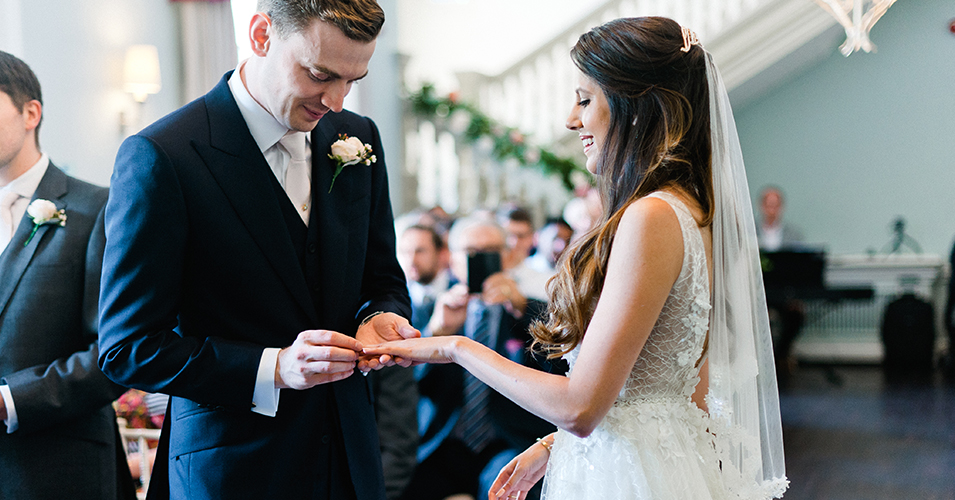 The grooms puts the ring on the brides finger at their wedding ceremony at Morden Hall in London