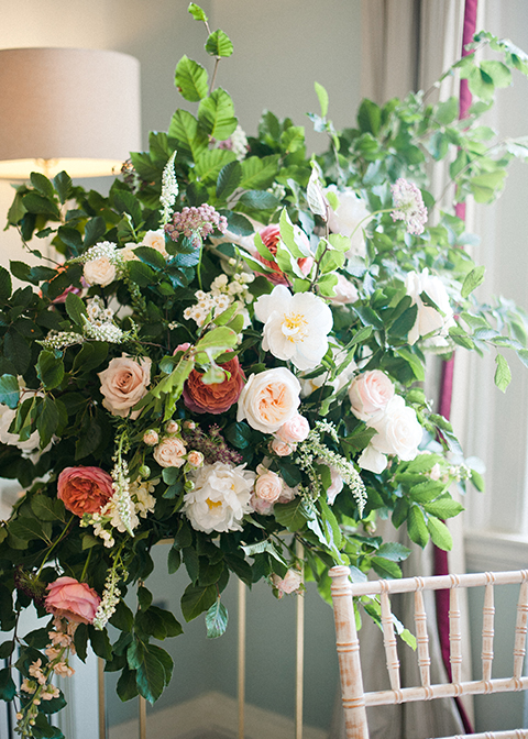 The ceremony room was decorated with arrangements of pretty pink rose roses and lots of lush green foliage at Morden Hall in London