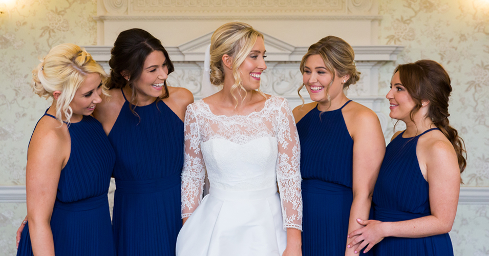 The bride wore a beautiful lace top wedding dress and the bridesmaids wore elegant navy blue dresses at this Morden Hall wedding