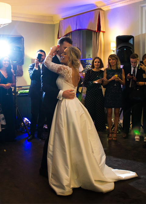 The happy couple take to the floor for their first dance as their guests watch on at this Morden Hall wedding
