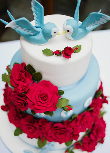 This bright pretty blue wedding cake has been adorned with lots red sugar roses for an alternative look at your Morden Wedding