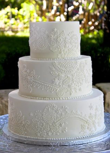 This white iced cake has cake has been decorated with a lace pattern to match the wedding dress at this wedding at Morden Hall in London