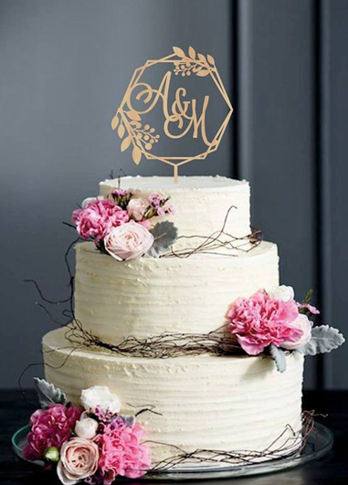 This pretty wedding cake has been decorated with fresh flowers and a monogrammed cake topper and is perfect for a wedding a Morden Hall