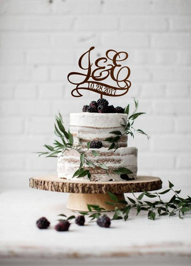 This semi-naked wedding cake has been decorated with fresh fruits and finished with a monogram topper at Morden Hall
