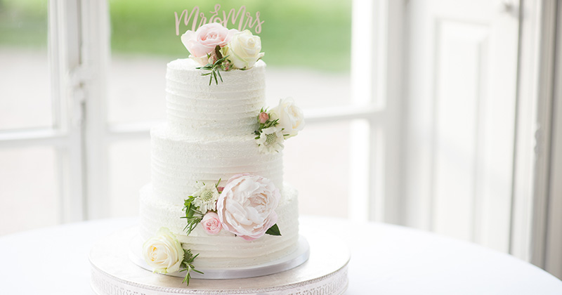 This beautifully white iced wedding cake has been simply decorated with pale pink roses and peonies at Morden Hall
