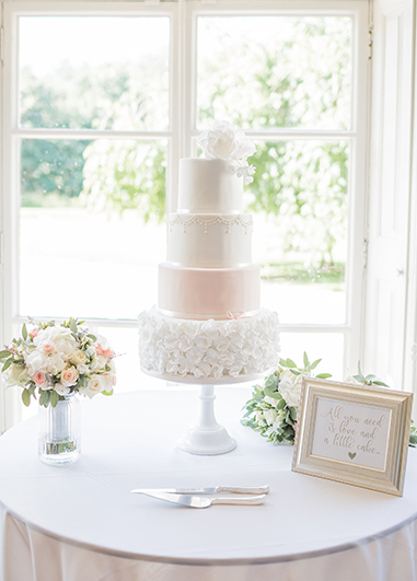This pretty four tier wedding cake has been decorated with sugar beading detail and sugar flowers at Morden Hall in London