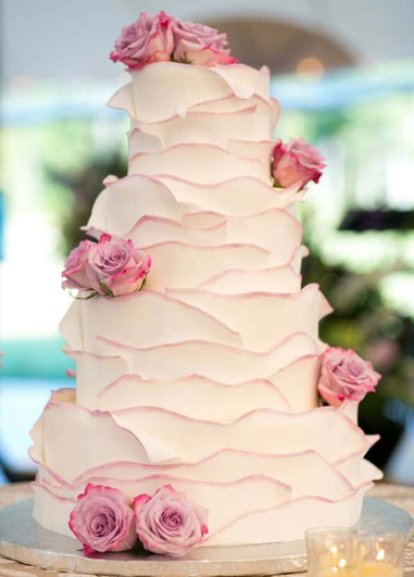 This wedding cake has been beautifully decorated with ruffles of icing to match the detail on the bride's dress at Morden Hall in London