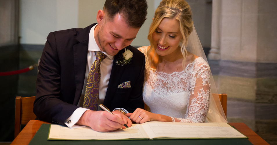 The happy newlyweds sign the register at their country house wedding in London