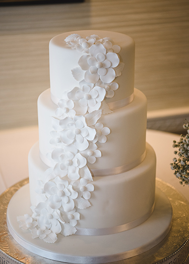 This white iced wedding cake has been decorated with pretty white sugar flowers at this country house wedding in London