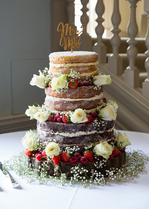 The couple chose a three-tier naked wedding cake decorated with fruit and fresh flower for their wedding at Morden Hall