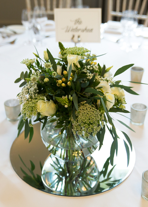 The couple chose vases of pretty white wedding flowers and lush greenery as their table centrepieces for their winter wedding in London