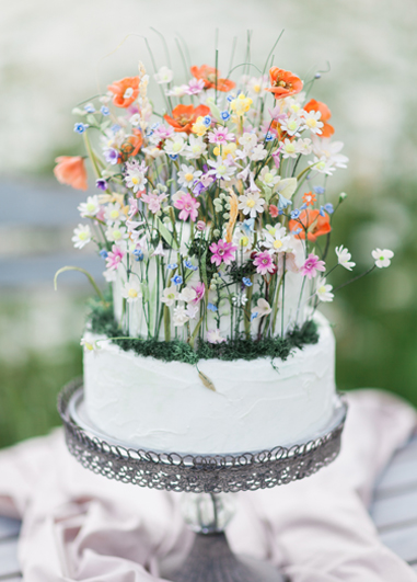 This two tiered white iced wedding cake is just stunning with masses of pretty sugar flowers giving that just picked look