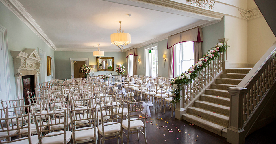 Pretty spring flowers adorned the staircase and lined the wedding aisle at this wedding ceremony at Morden Hall