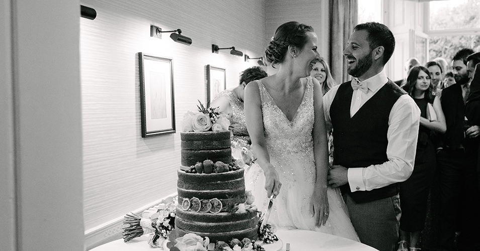 The bride and groom cut their naked wedding cake at this spring wedding at Morden Hall