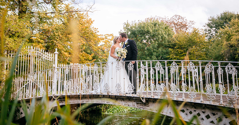The happy newlyweds pose for a wedding photo on the bridge at Morden Hall in London