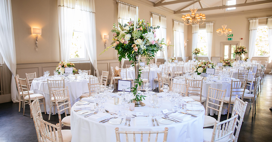 Tall candelabras and large arrangements of beautiful spring flowers were used as wedding table centrepieces at this London wedding venue.
