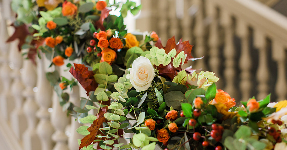 A garland of beautiful autumnal flowers and foliage was used to decorate the staircase at this Morden Hall wedding