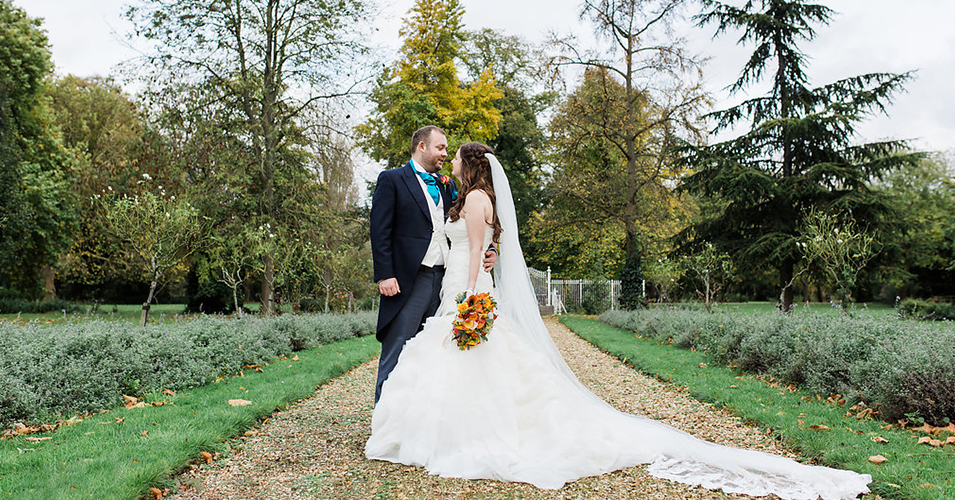 The happy newlyweds pose for a wedding photo in the gardens at this country house wedding venue in London