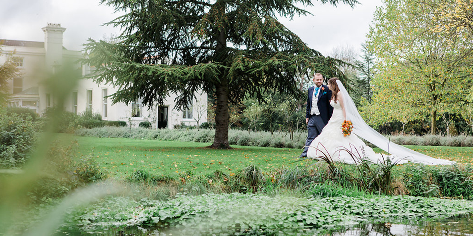 The happy newlyweds go for a stroll through the gardens at their Country House wedding in London