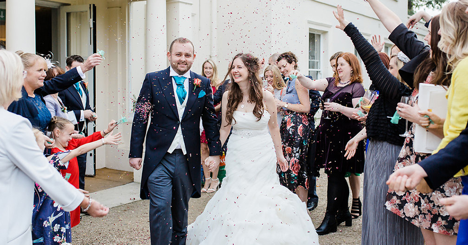 Guests throw confetti over the happy couple at their autumn wedding at Morden Hall in London
