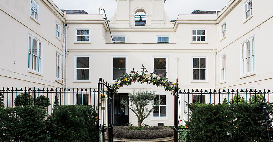 The gate arch was decorated with pretty florals at this country house wedding at Morden Hall in London