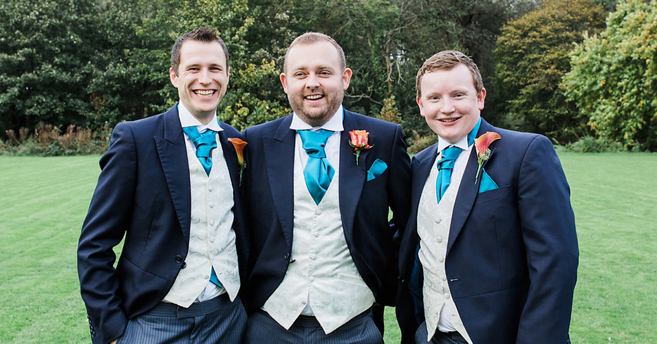 The groom and groomsmen wore navy wedding suits with cream waistcoats, teal ties and burnt orange buttonholes at Morden Hall