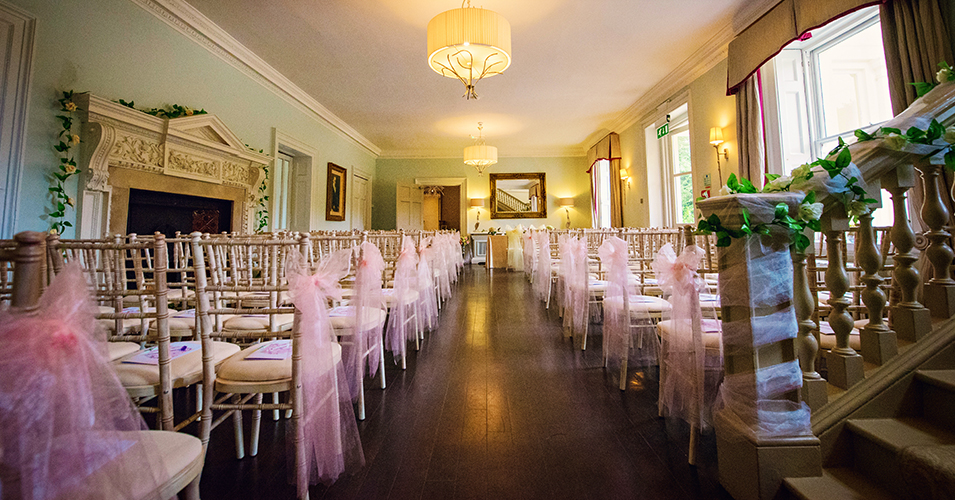 Pretty pink tulle bows were tied to the chairs at the end of the wedding aisle at Morden Hall