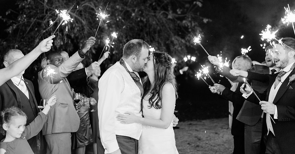 The happy couple enjoy a moment as their guests hold sparklers around them at Morden Hall.