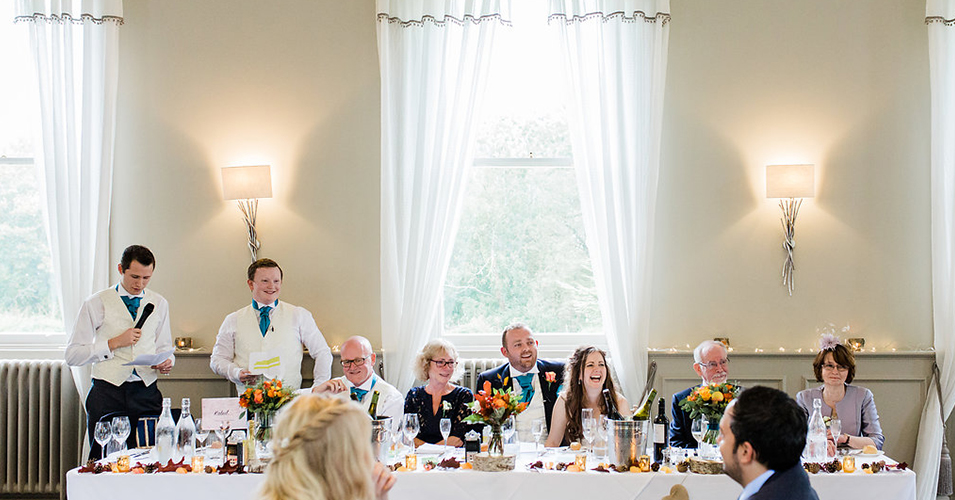 The happy couple and wedding party enjoy the speeches at this autumn wedding at Morden Hall in London