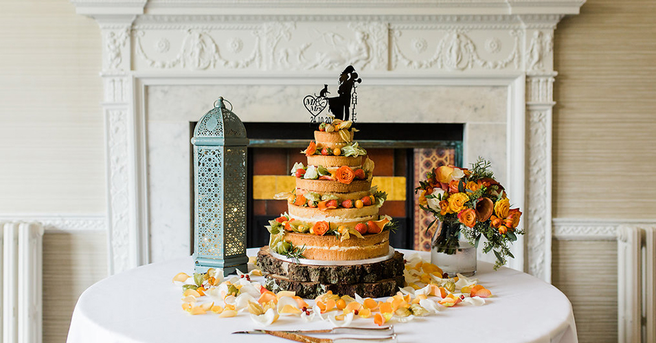 The couple chose a naked wedding cake decorated with seasonal fruits at their autumn wedding at Morden Hall