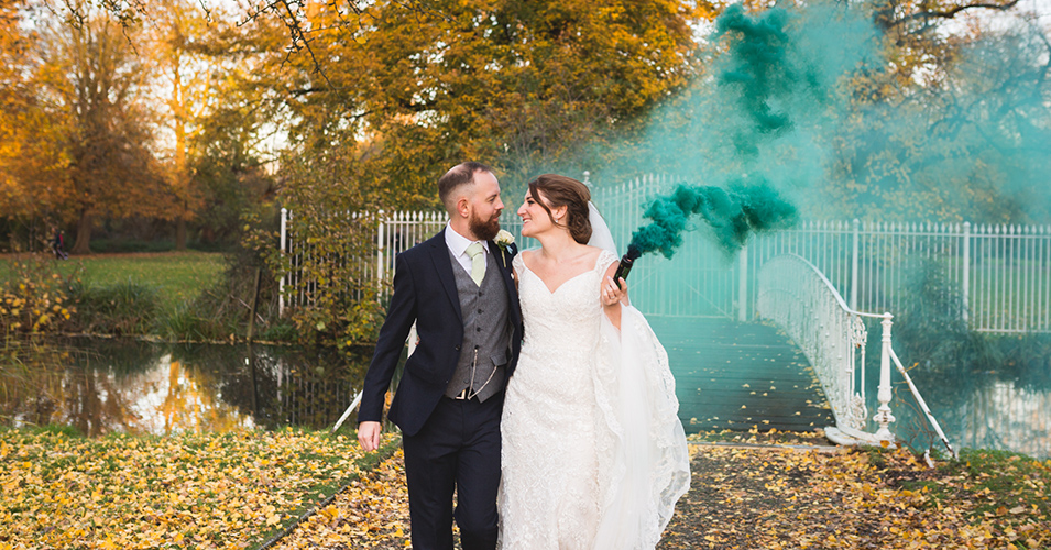 The happy couple have their photo taken in the gardens at their autumn wedding at Morden Hall