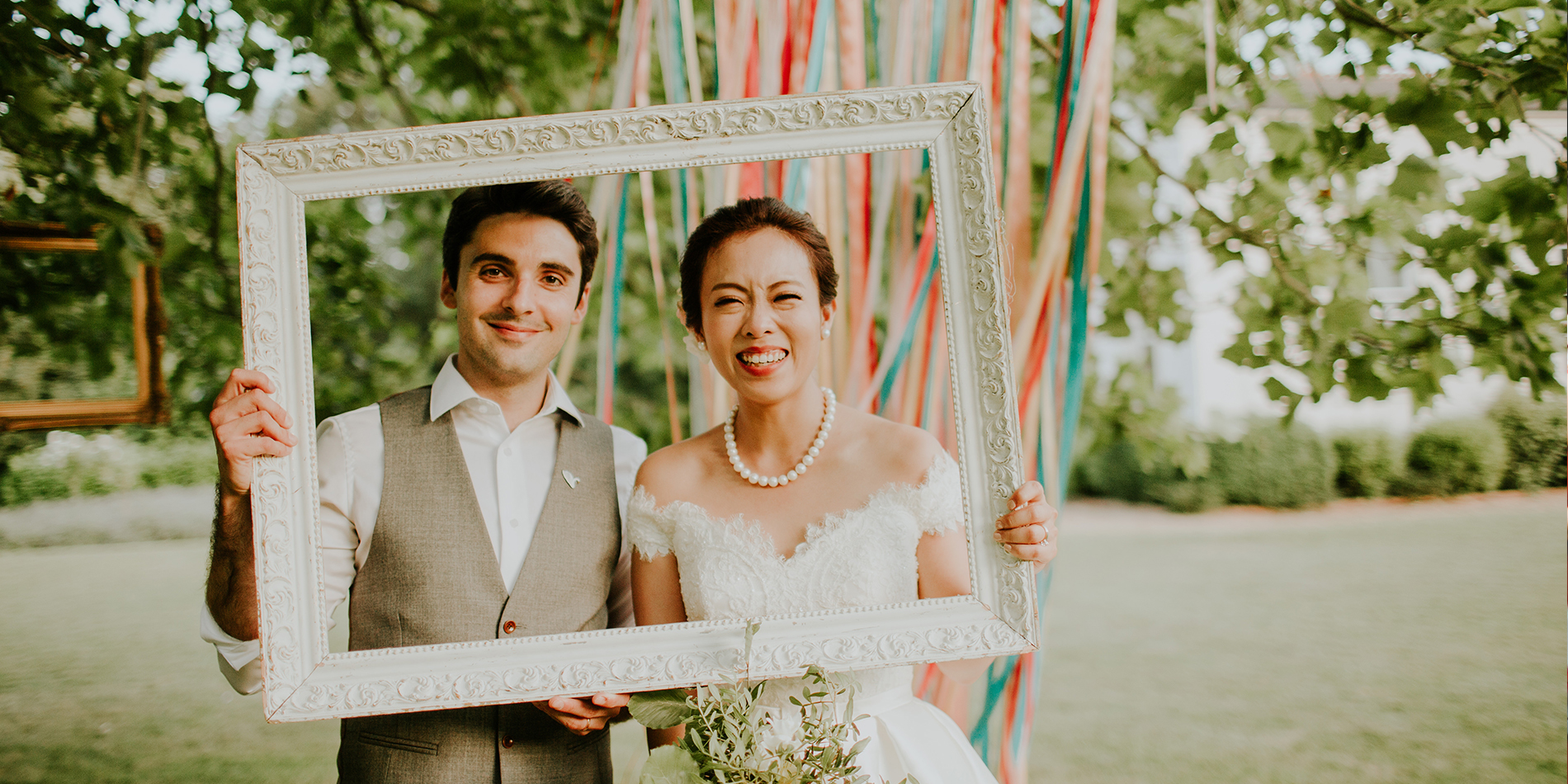 The wedding couple use a large picture frame as a fun wedding photo prop at their Morden Hall wedding
