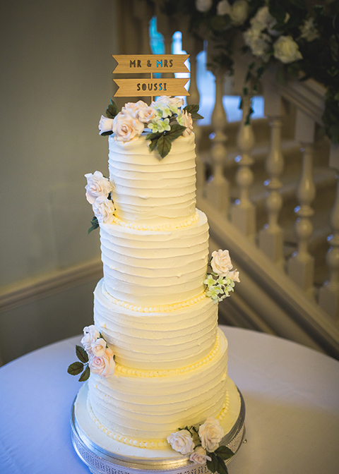 The couple chose a four-tiered white iced wedding cake decorated with pretty sugar flowers for their wedding at Morden Hall
