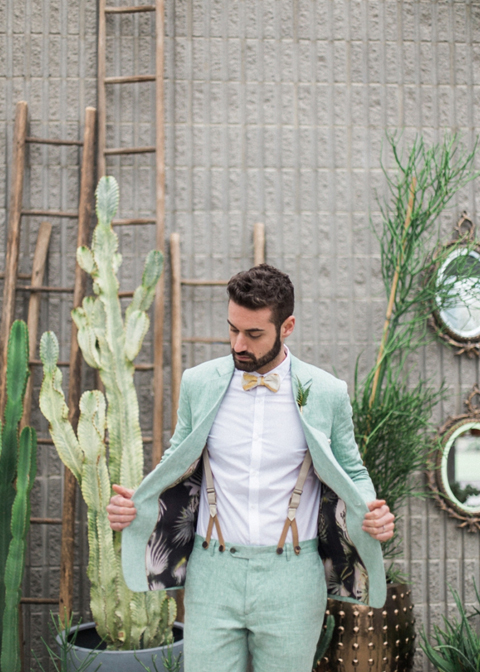 This groom chose a pastel wedding suit with braces for his summer wedding in the city