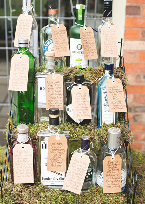 Old gin bottles were used as a wedding table plan at this country house wedding