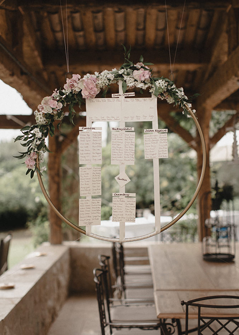 This original table plan is made from a metal hoop and decorated with wedding flowers