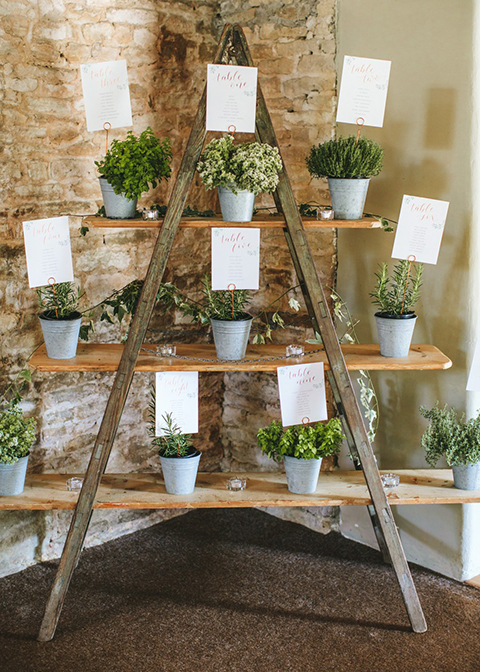 The ladder table plan is decorated with mini plant pots at this wedding in London