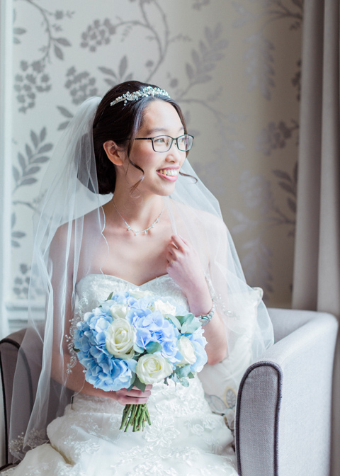 A bride holds a beautiful wedding bouquet of blue hydrangeas
