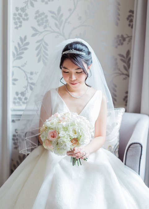 The bride holds a beautiful wedding bouquet of white flowers