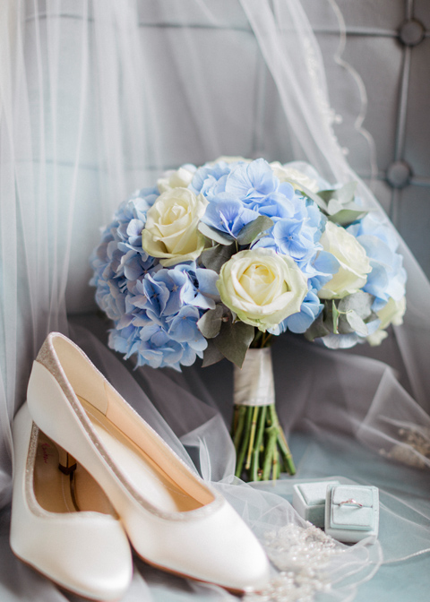 A close up of the bride's wedding shoes and blue hydrangea wedding bouquet