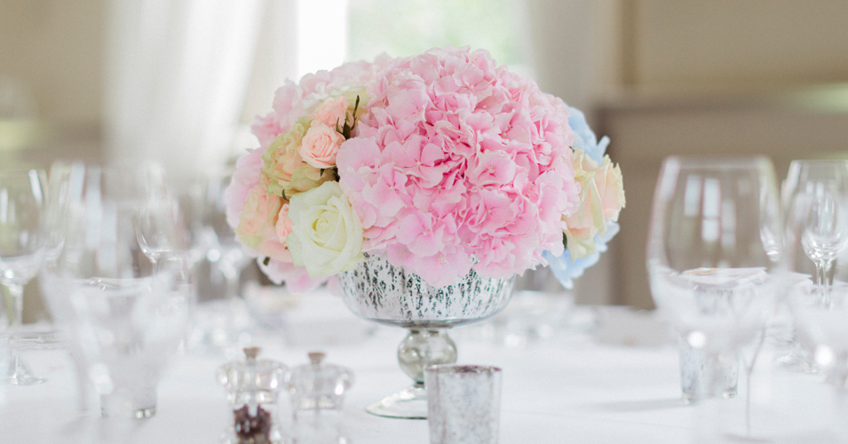 Beautiful pastel coloured flowers in spackled vases adorned the tables