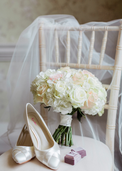 A close up of the white wedding bouquet and wedding shoes