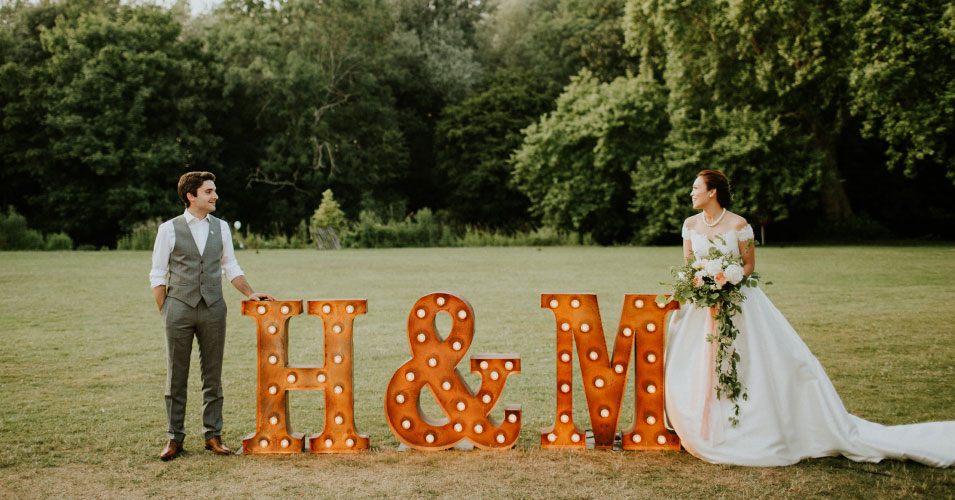 Bride and groom stand by illuminated love letters