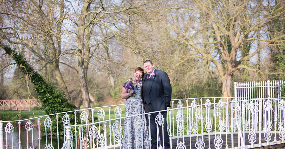 Bride and groom stand on bridge at Morden Hall