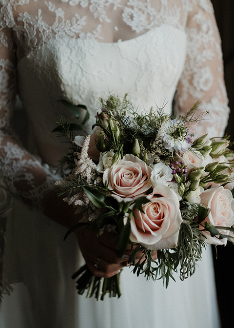 Ruth holds her wedding bouquet featuring pink and green flowers