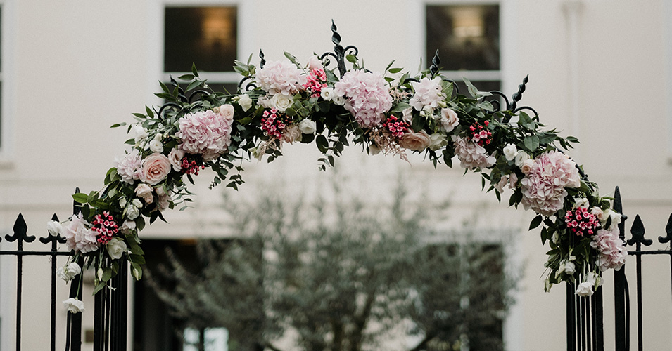 A floral arch decorates the entrance of this exclusive wedding venue