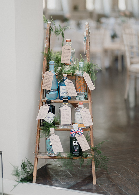 The couple decorated a ladder with gin bottles to present their table plan