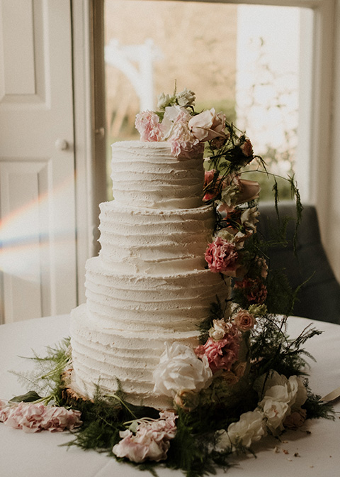 A beautiful four-tiered wedding cake decorated with flowers